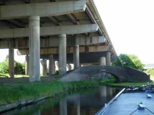 The traditional Blakeley Hall Bridge under the elephantine legs of the M5