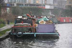 Strange craft - a narrowboat with a flat platform bolted on and heaped with stuff....