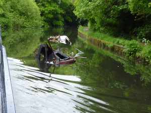 Sad blot on the canalscape - a ruined boat well out in the navigation - looked totally burned out :-(